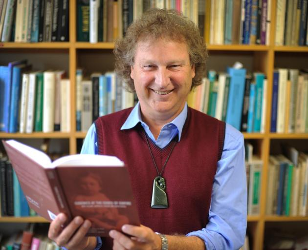 University of Otago academic Hamish Spencer with a copy of the new book he co-authored on the...