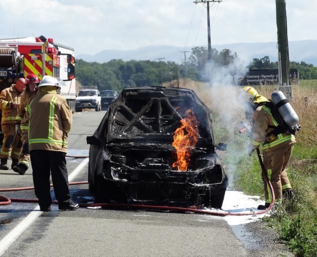 Firefighters work to extinguish a car fire at Totara, south of Oamaru, yesterday afternoon. PHOTO...
