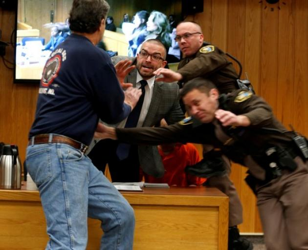 Father lunges at Larry Nassar in court this morning