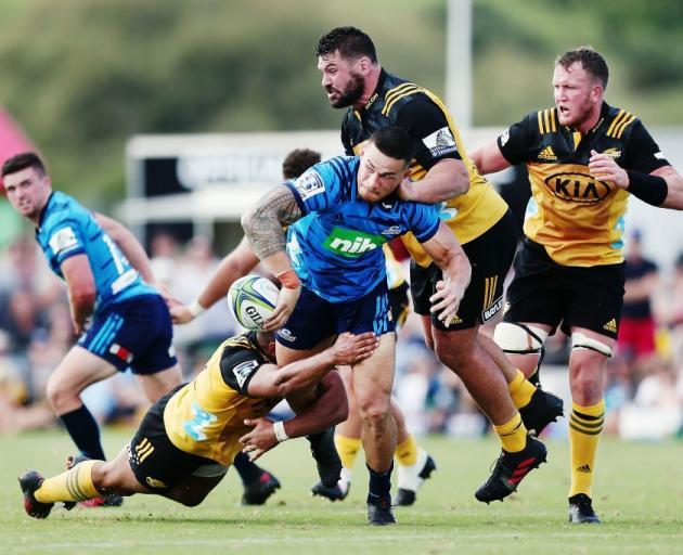 Blues second five-eighth Sonny Bill Williams offloads in a tackle during their preseason game...