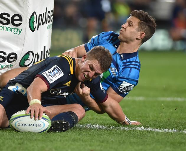 Highlanders second five-eighth Tei Walden, in the tackle of Blues winger Matt Duffie, grounds the ball for a try in their opening Super Rugby match at Forsyth Barr Stadium in Dunedin last night. Photo: Gregor Richardson