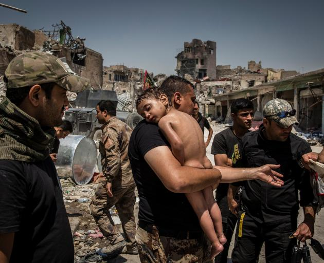 An unidentified young boy, who was carried out of the last IS-controlled area in the Old City of Mosul by a man suspected of being a militant, is cared for by Iraqi Special Forces soldiers last year. Photo: Reuters