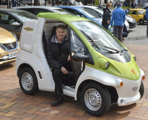 Car salesman Ivan Webster displays a Toyota Coms electric vehicle in the Octagon yesterday.