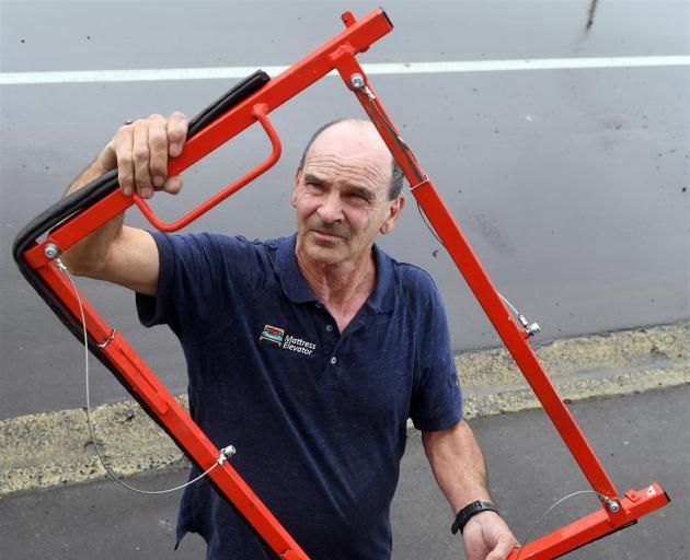 拉里·伯恩斯(Larry Burns)展示了他设计的阻止洪水通过门口的设备。照片:Stephen Jaquiery