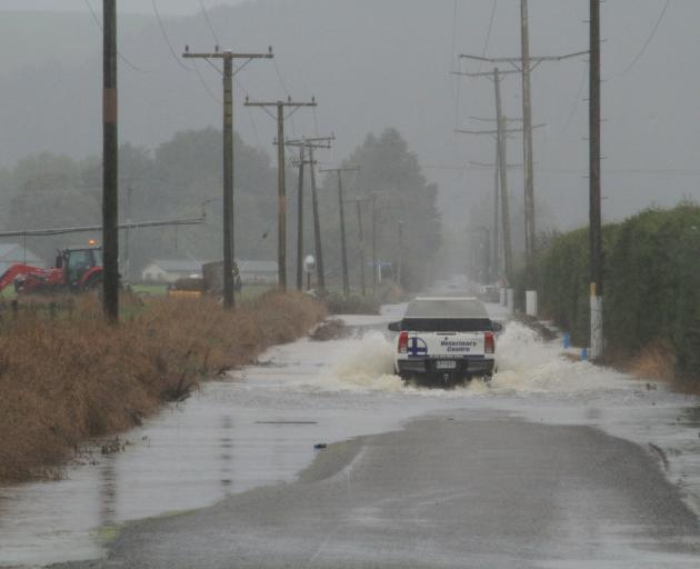 Farm traffic continues to use a flooded Papakaio Rd, north of Oamaru, on Wednesday. Photo: Hamish...