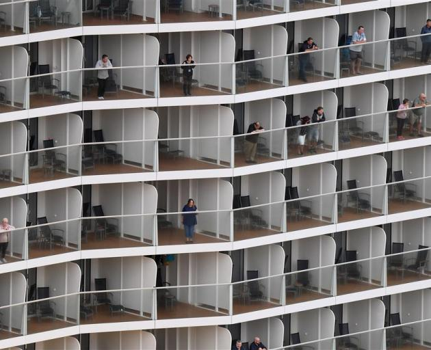 Passengers line their suite balconies as Ovation of the Seas docks at Port Chalmers yesterday...