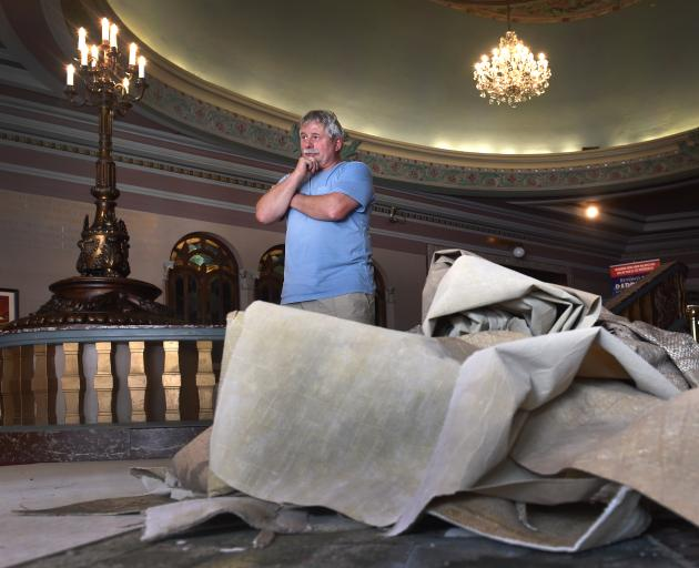 Regent Theatre technical manager Nelson Miles supervises the removal of flood-damaged carpet...