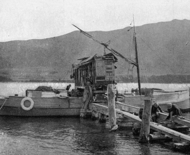 A threshing mill being loaded on to an oil launch at Pembroke, Lake Wanaka, to be taken to Mr...