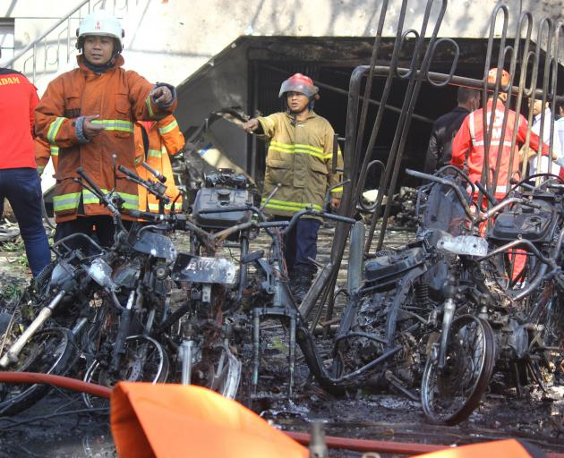 Firefighters are seen at the site of a blast at the Pentecost Church, Central Surabaya. It is...