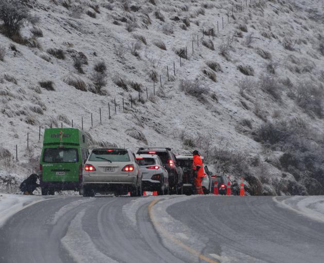 Motorists on the Crown Range Rd yesterday had to fit chains before the summit after snow fell on the popular Wanaka-Queenstown link. Photo: Sean Nugent