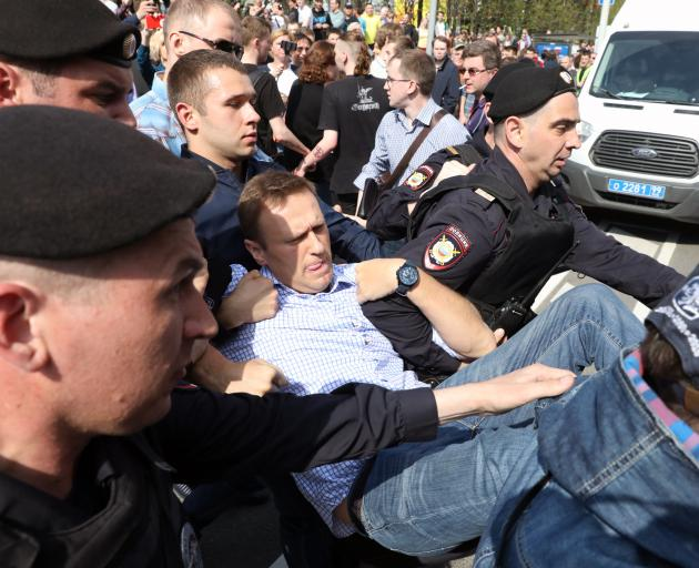 Russian opposition leader Alexei Navalny is carried away by police during protests against the...