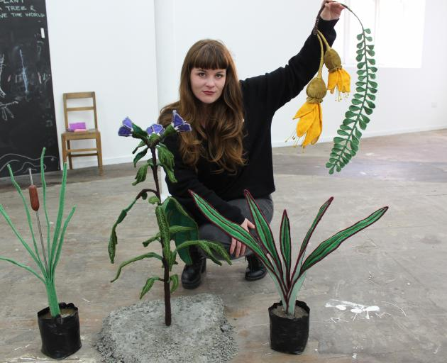Ruth Evans displays plants she created with a range of techniques and from mostly recycled material. They are poroporo (left), harakeke and she is holding kowhai. PHOTO: ELLA STOKES