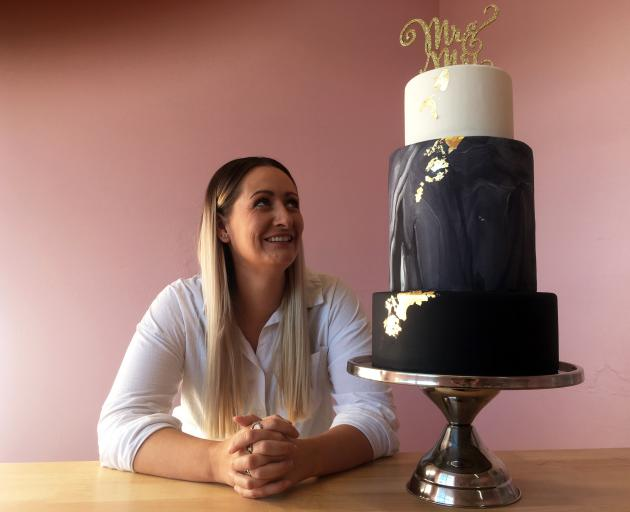 Williams & Co Kitchen Ltd owner Tess Williams inspects a wedding cake in her new shop in Mornington. Photo: Shawn McAvinue