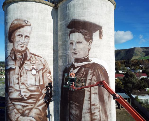 Waimate artist Bill Scott works on murals on grain silos at Transport Waimate's Queens St yard. The murals are of Waimate-born World War 2 soldier Eric Batchelor and New Zealand's first woman to be registered as a doctor, Margaret Cruickshank, who practis