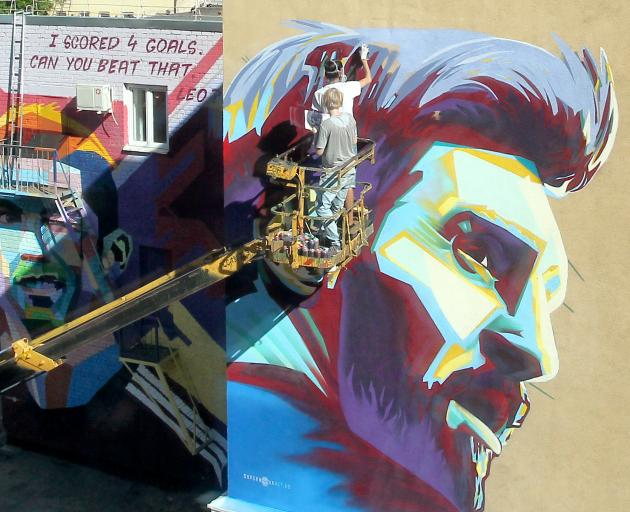 A mural of Argentina's Lionel Messi is painted next to a mural of Portugal's Cristiano Ronaldo. Photo: Reuters