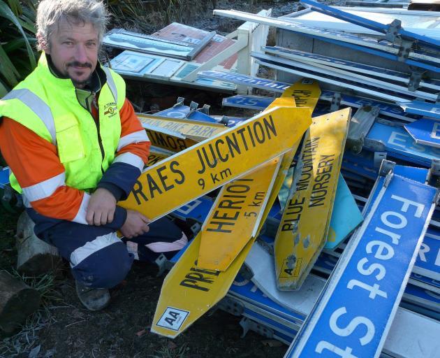 Tapanui auction organiser Brendon Stuart holds the misspelt Raes Junction sign which sold for $590. Photo: Richard Davison