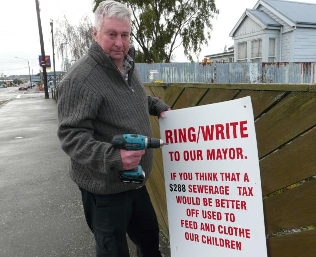 Balclutha pensioner Bruce Graham takes down his protest sign in Clyde St yesterday, after claiming victory in a three-year rates battle with the Clutha District Council. Photo: Richard Davison