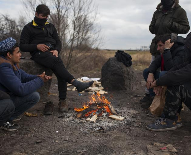 A group of young migrants warm themselves near a campfire on an industrial estate in Calais,...