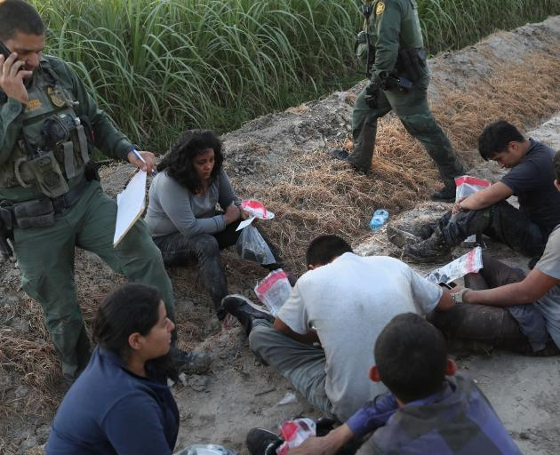 Border Patrol agents watch over a group of undocumented immigrants after chasing and apprehending...