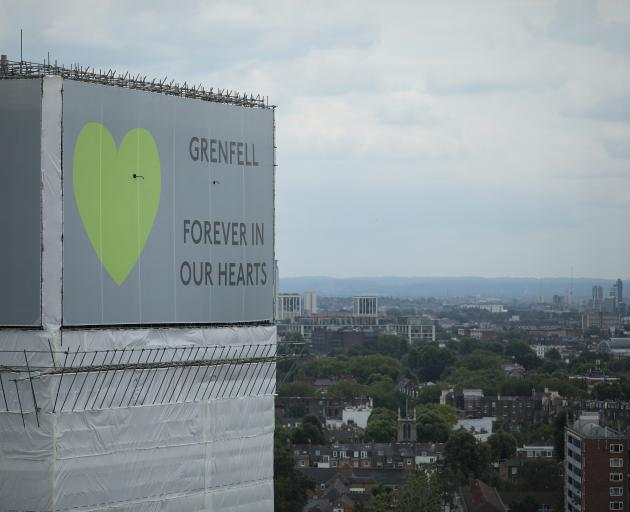 A sign with 'Grenfell Forever In Our Hearts' is displayed on the top of Grenfell Tower on June...