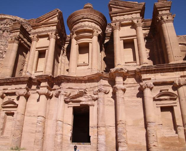 A tourist is dwarfed by the rock-sculpted mammoth Monastery, set on a hilltop in Petra. Photo: TCA