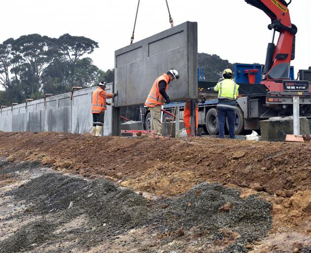 Concrete panels for the wave wall being lifted into place on the crest at Ross Creek dam...