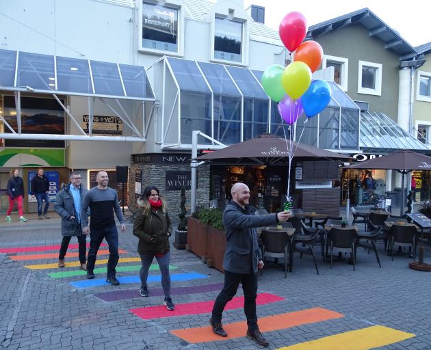 Winter Pride co-director Martin King (right) is followed by Anya Henarath, Winter Pride co-director Mike Hughes and Craig Watson on Queenstown's new rainbow crossing, officially opened by Queenstown Lakes Mayor Jim Boult last night. Photo: Tracey Roxburgh
