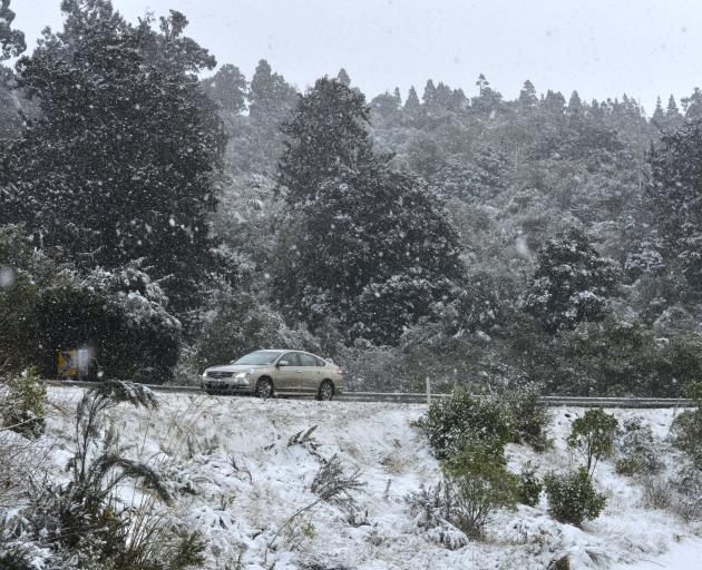 A motorist drives through a snow flurry on Dunedin's northern motorway this morning. Photo:...