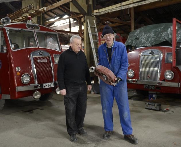 Dunedin Fire Brigade Restoration Society president Joe Hayde (left) and vice-president Gary Byford, who holds spare parts, stand beside two Dennis fire appliances built in the 1950s, one from Roxburgh and the other from Balclutha. Photos: Gerard O'Brien