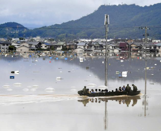 Residents are rescued from a flooded area by Japan Self-Defence Force soldiers in Kurashiki....