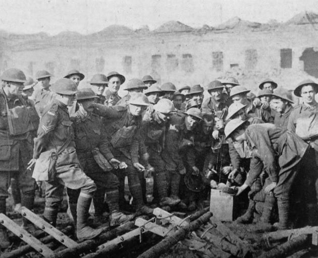 Australian troops receiving their rations in a ruined town, near the front in France. - Otago...
