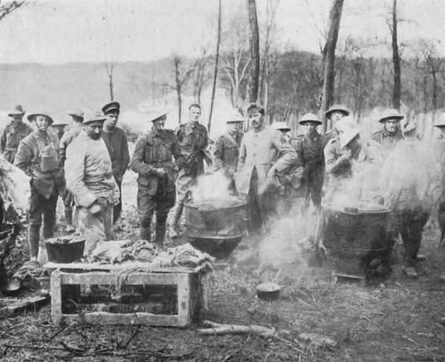 The entente cordiale: British and French soldiers cooking together in a wood during the April German attack. - Otago Witness, 3.7.1918.