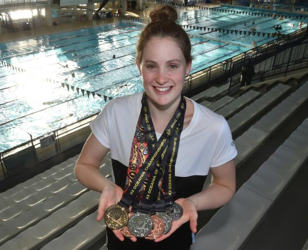 Caitlin Deans (18) at Moana Pool yesterday, holds the six medals she won at the Oceania Championships. Photo: Gregor Richardson