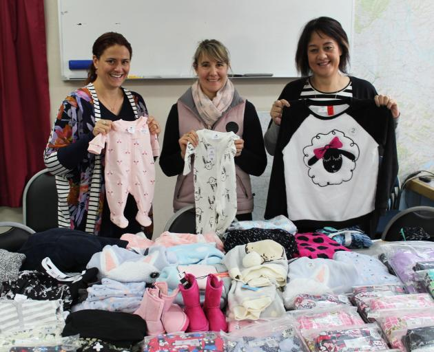 One hundred sets of pyjamas all ready to be packed up for Foster Hope Otago thanks to three generous ladies - (from left) Nicola Ryan, Kate Hurring and Emma Hutton. Photo: Ella Stokes