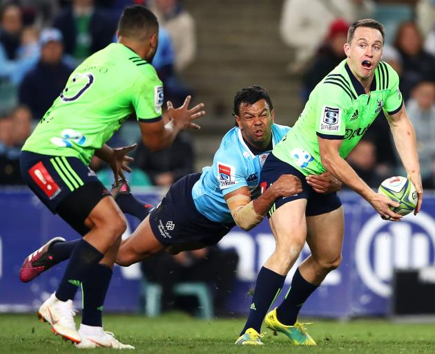 Highlanders fullback Ben Smith offloads to first five-eighth Lima Sopoaga in the tackle of...