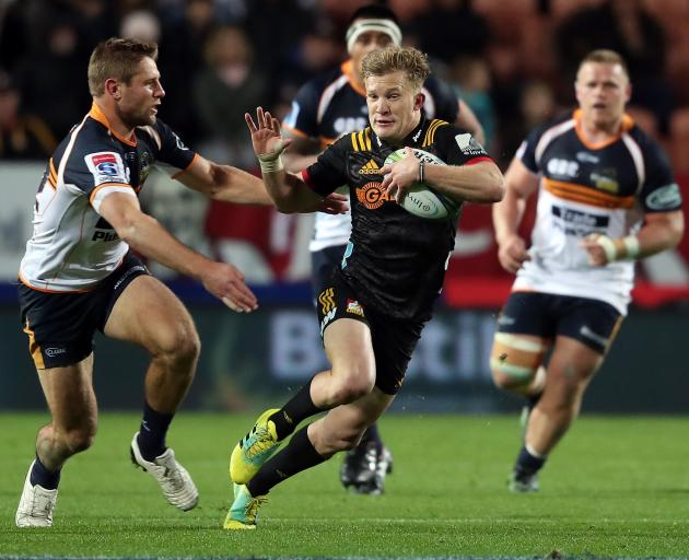 Damian McKenzie looks to fend off the tackle. Photo: Getty Images