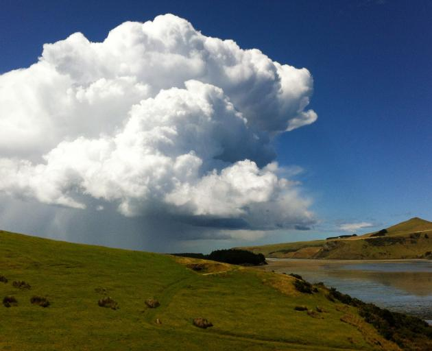 A striking towering cumulus cloud rising up to the east beyond the mouth of Papanui Inlet and Victory Beach on the Otago Peninsula. Photo: Helen Sheppard