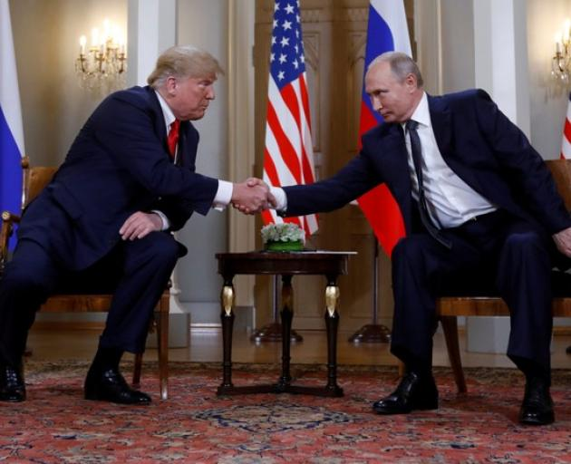 US President Donald Trump and Russia's President Vladimir Putin shake hands as they meet in Helsinki, Finland. Photo: Reuters