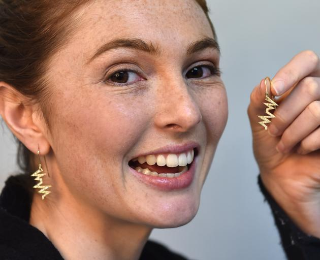 Otago Polytechnic student Alesha Pyers poses with the diamond-studded gold heartbeat earrings she designed, which will be auctioned for charity later this month. Photo: Peter McIntosh