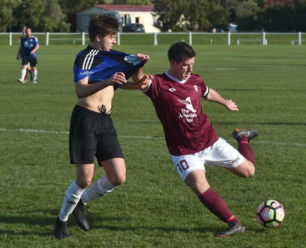 Dunedin Technical's Andy Coburn (right)  looks to clear the ball ahead of Queenstown Rovers' Alex...