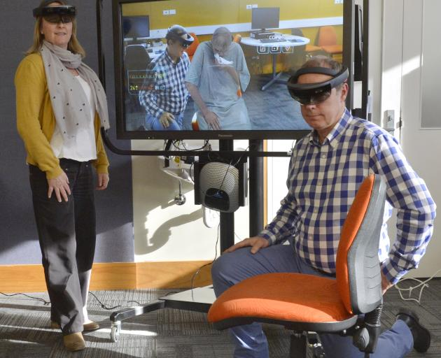 Nursing School head Ian Crabtree kneels beside a seated holographic patient, who is invisible to...