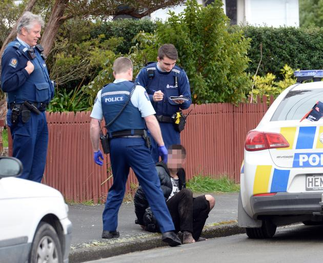 A man talks to police after being apprehended in Tasman St following a foot pursuit through streets and gardens in the Dunedin suburb of Liberton. Photo: Staff Photographer