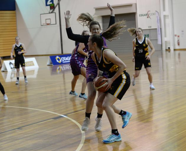 Ajax player Danielle Frost (front) takes on Claudia Flaws, of the South Pacific Magic, in the Dunedin women's premier basketball final at the Edgar Centre last night. Photo: Linda Robertson