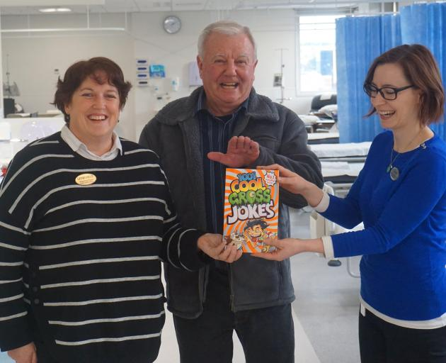 Mosgiel resident Warren Wenlock (centre) hands over a joke book to Bowel Screening nurse co-ordinators Genevieve Cowley (left) and Laura Bane (right) at Dunedin Hospital recently. Photo: Supplied