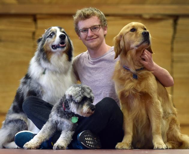 University of Otago student Finnbar Grieve (19) chills with friendly dogs (from left) Martin, ...