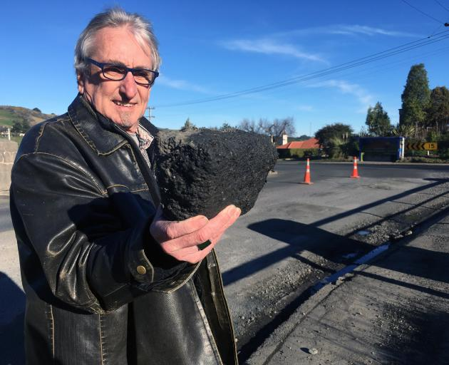 Rob Fitzpatrick inspects a chunk of asphalt left behind after a temporary repair of a bridge deck in Abbotsford. Photo: Shawn McAvinue