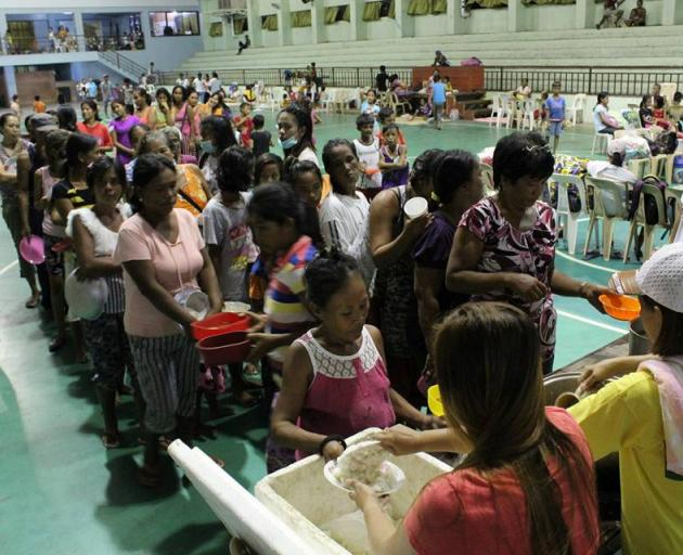 People are seen inside an evacuation centre in preparation for Typhoon Mangkhut in Cagayan,...