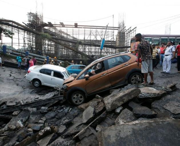 People stand next to the wreckage of vehicles at the site of a bridge that collapsed in Kolkata. Photo: Reuters