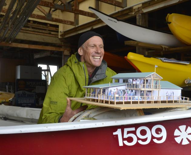 Broad Bay Boating Club rebuild committee member Chris Charteris-Wright shows off a model of the club's planned redevelopment, inside the club's now inadequate boat storage facility. Photos: Gerard O'Brien
