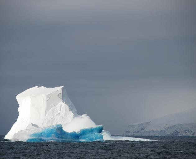 White and blue icebergs float just offshore of the East Antarctic, where the East Antarctic Ice...